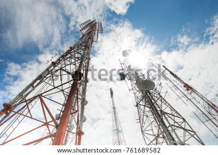 Telecommunication towers include of radio microwave and television antenna system with cloud blue sky and sun ray.