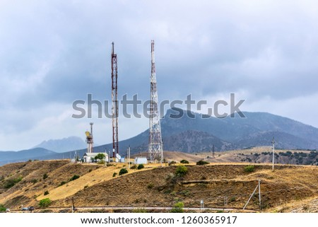 Telecommunication towers on a background of mountains. Cellular. Highway. #1260365917