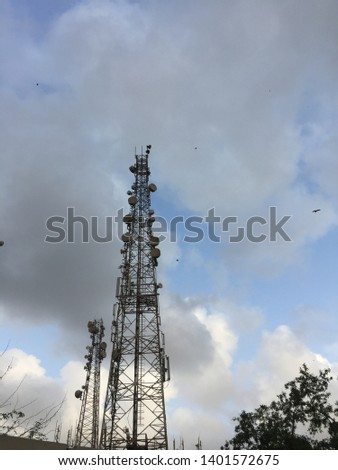 Telecommunication wireless signal technology towers with clouds #1401572675