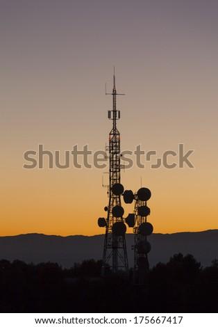 telecommunications antennas silhouettes, backlit