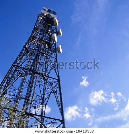 Telecommunications mast set against blue sky and small clouds