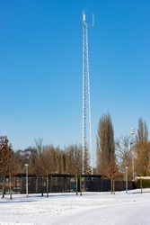 telecommunications tower in the winter with a layer of snow in the foreground under a clear blue sky