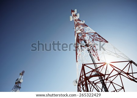 Telecommunications tower with clear blue sky.