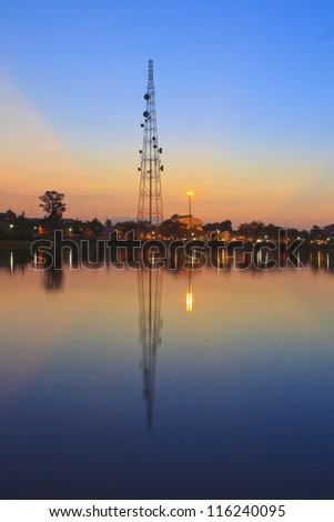 Telecommunications towers near the secret sky after the Sun's reflection in a pond.