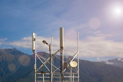 Telecommunications transmitters 4G, 5G. cellular base station with transmitter antennas near the road on the background of mountains.