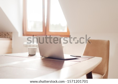 Telecommuting workspace with laptop and smartphone, selective focus #1571201701
