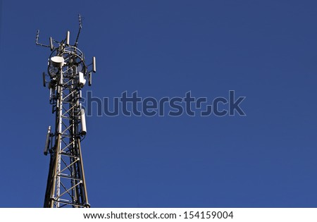 Telecoms/cellphone mast; isolated against deep blue sky; excellent and extensive copy-space