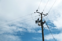 Telegraph pole with cables against a cloudy sky