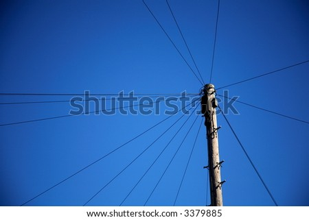telegraph pole with wiring isolated against deep blue sky