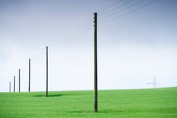 Telegraph poles and telephone communication cables through green field