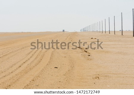 Telegraph poles beside a road stretch out as far as you can see, showing the curvature of the earth.  Namib Desert, Namibia