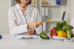 Telehealth and online nutritiologist concept. Woman doctor nutritiologist sitting and pointing at fresh vegan healthy ingredients to patient online during videocall or distant meeting