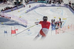 Telemark skier competing in downhill race, seen from the back while rushing towards the finish line