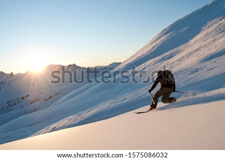 Telemark skiers doing late afternoon tour in the mountains of Kleinwalsertal in austrian alps #1575086032