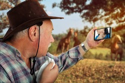 Telemedicine app lets a medical woman treat her rural patient remotely via video-chat. The old cowboy looks to the doc on the screen of his mobile phone. She shows how to check the pulse on the neck.