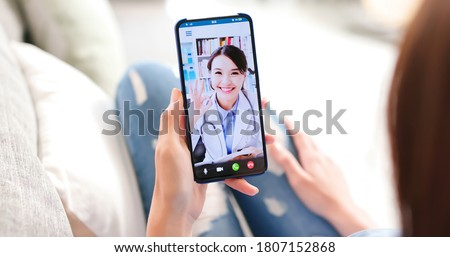 Telemedicine concept - back view of asian woman has video chat with female doctor and she make a discussion with ok gesture