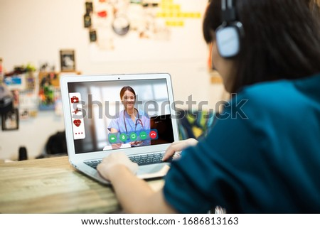 telemedicine concept,back view of female with laptop during online medical consultation with her doctor via video call
