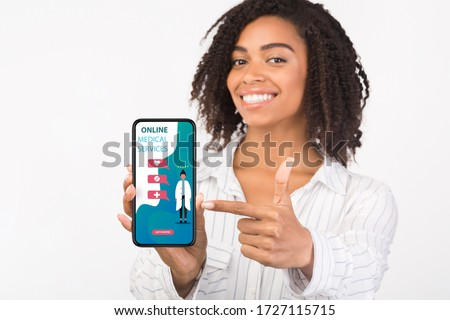Telemedicine Concept. Closeup of black patient pointing at phone with online medical services on the screen, isolated