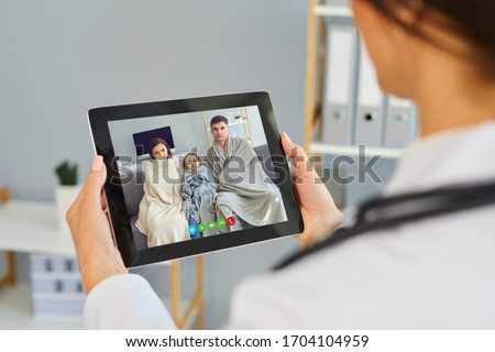 Telemedicine concept. Family doctor online call. Shoulder view doctor therapist speaks with a sick family video chat using a tablet in a clinic office.