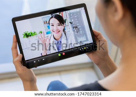 telemedicine concept- patient use tablet to has video chat with asian female doctor
