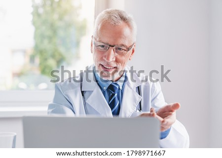 Telemedicine. Senior doctor making video call or live video on social network with patient or student while sitting on modern office in hospital
