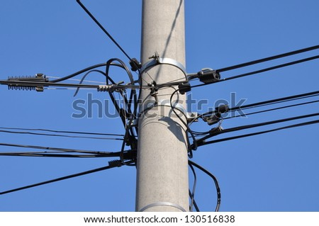 Telephone cable lines on a pole against a blue sky