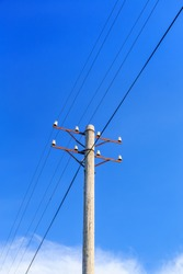 Telephone pole with wires against a blue sky