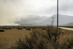 Telephone poles along a road where smoke from the Creek Fire moves northward in the Owens Valley, obscuring the Sierra Nevada.
