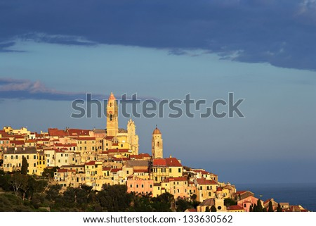 Telephoto view of Cervo old town, Liguria, Italy, with the beautiful baroque church arising from the houses, under evening warm sunlight.