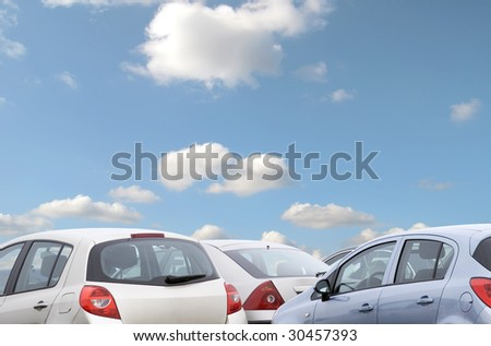 Telephoto view of parked cars with blue cloudy sky