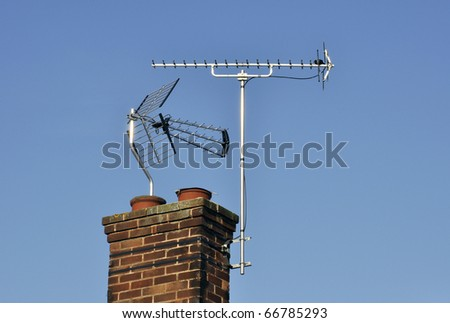 Telephoto view of television aerials mounted on chimney