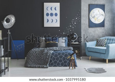 Telescope near bed with knit blanket against dark wall with star stickers in blue bedroom interior