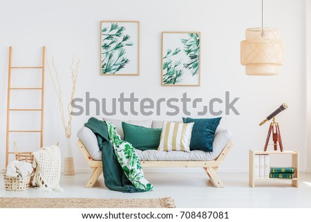 Telescope on wooden table in living room with dark green accents and paintings with floral motif