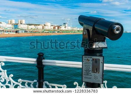 Telescope or binoculars coin for traveler, visitor or tourist at Brighton Pier with Brighton Pier landmark in background. #1228336783