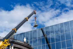 telescopic boom of a construction crane lifts the load against the mirror wall of the building reflecting the sky