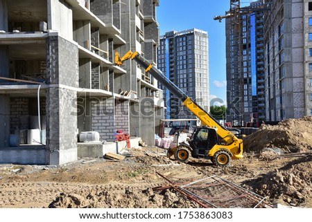 Telescopic handler work at the construction site. Construction machinery for loading. Tower crane during construct a multi-storey residential building. Wheel loader for lifting goods Foto stock ©