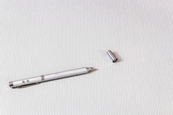 Telescopic pen with laser pointer for teaching and presentation on a light background.