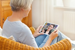 Teletherapy concept, senior woman talking with her counselor or laywer during a live call on her tablet pc at home
