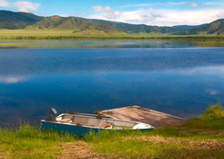 Teletskoye Lake, Altai Republic, Southern Siberia, Russia. Panoramic view of famous Lake Teletskoye  with fishing boat surrounded by the majestic mountain range of Altay against a clear blue sky