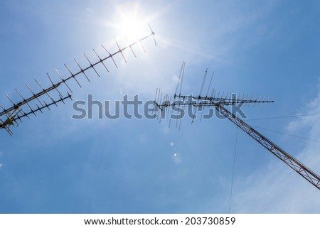 television antenna and the sun on blue sky background and lens flare