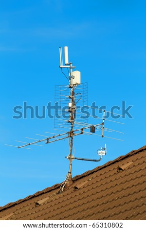 television antenna and wi-fi transmitter on the roof - stock photo