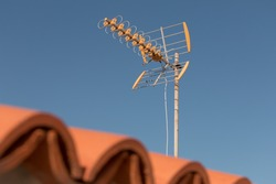 television antenna on a rooftop in front of blue sky