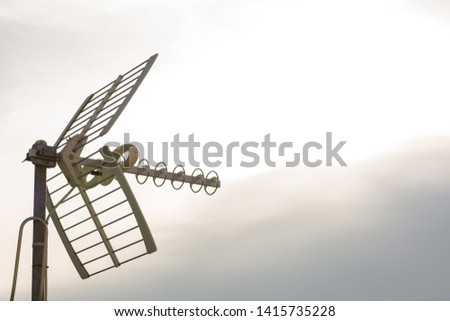 television antennas with sky background. Analog television antenna on roof. Antennae for digital TV and radio reception. Mobile communication antennas at sunset. #1415735228