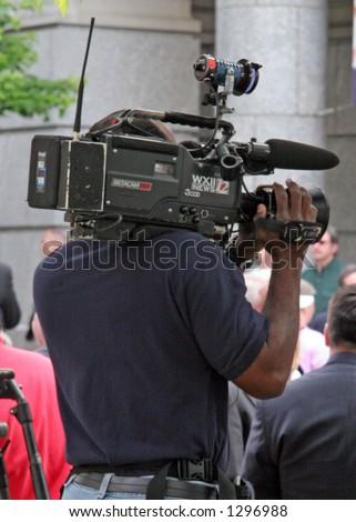 Television camera person recording outdoor event
