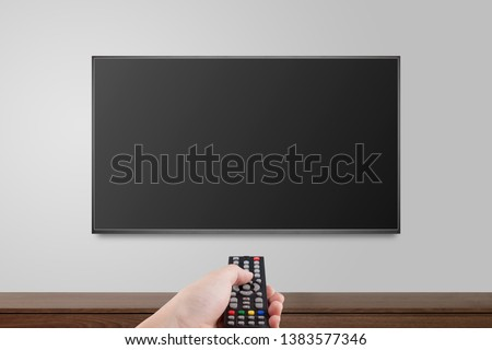 Television on white wall with hand using remote control, TV 4K flat screen lcd or oled, plasma realistic illustration, Black blank HD monitor mockup, Modern video panel black flatscreen. #1383577346