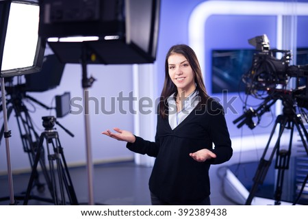 Television presenter recording in television news studio.Female journalist anchor presenting business report.News camera,light equipment behind the scenes.Talking at camera to the TV audience.