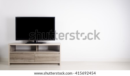 Television put on wood table, background white wall. #415692454