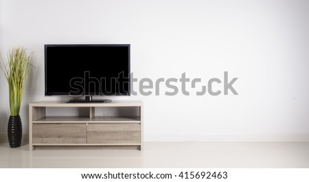 Television put on wood table, background white wall.