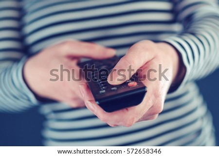 Television remote control in female hands pointing to tv set and turning it on or off