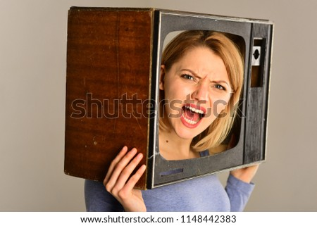 television set. television set on head of angry woman. woman hold television set in hands. television set and new technology. bang #1148442383